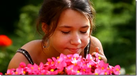 stock-footage-young-beautiful-girl-smelling-pink-flowers-smiling-closeup